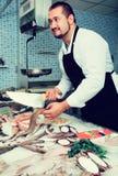 Vendeur avec des poissons de coupe de couteau Image stock