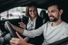 Vendeur avec le client au concessionnaire automobile Image stock