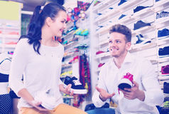 Vendeur d'homme aidant la fille en choisissant des espadrilles Image stock