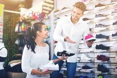 Vendeur d'homme aidant la fille en choisissant des espadrilles Photo stock