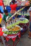 Vendeur de bord de la route vendant les mangues crues coupées avec la poudre de prune Photographie stock