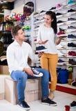 Vendeur de femme aidant l'homme en choisissant des espadrilles Images libres de droits