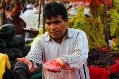 Vendeur de fruit donnant la pastèque coupée et rassemblant l'argent liquide images stock