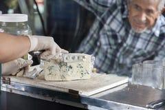 Vendeur de observation Slicing Blue Cheese d'homme dans la boutique Image libre de droits