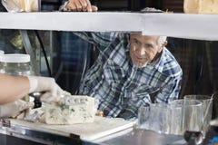 Vendeur de observation Slicing Blue Cheese d'homme dans la boutique Photo libre de droits
