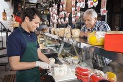 Vendeur de observation Slicing Cheese In d'homme heureux faire des emplettes Images libres de droits