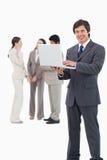 Vendeur de sourire avec l'ordinateur portable et l'équipe derrière lui Images stock