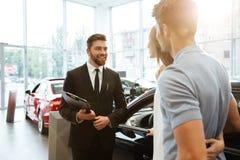 Vendeur de sourire montrant la nouvelle voiture à un couple photographie stock libre de droits