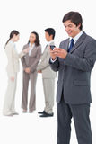 Vendeur de sourire tenant le téléphone portable avec l'équipe derrière lui Photos libres de droits