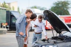 Vendeur de voiture au concessionnaire montrant le moteur à un client images libres de droits