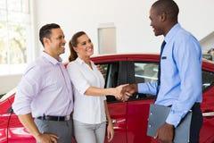 Vendeur de voiture de poignée de main de couples Photographie stock libre de droits