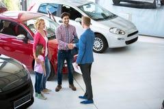 Vendeur de voiture montrant le nouveau véhicule aux clients Image stock