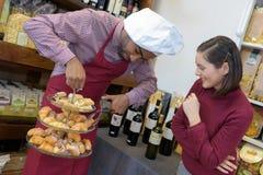 Vendeur donnant à conseil de femme sur la bouteille de achat le vin rouge Image libre de droits
