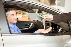 Vendeur donnant des clés à un homme d'affaires de sourire images stock