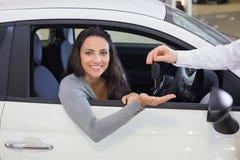 Vendeur donnant des clés à une femme de sourire image stock