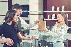 Vendeur donnant le sac de papier avec l'achat pour des couples Photographie stock libre de droits