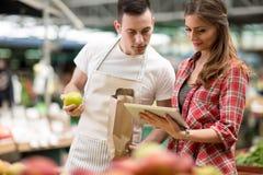 Vendeur et client regardant la liste de vérification sur le marché Image stock