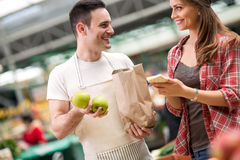 Vendeur et jeune femme regardant le marché Photos stock