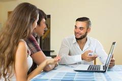 Vendeur et jeunes couples à la maison photographie stock libre de droits