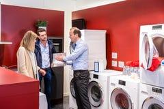 Vendeur Explaining To Couple dans le département de machine à laver Photos stock
