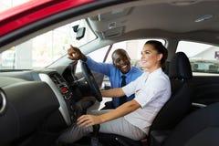 Vendeur expliquant des caractéristiques de voiture image stock