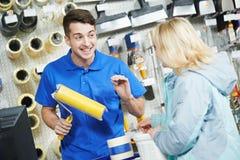 Vendeur expliquant le rouleau de peinture à l'acheteur Photos stock