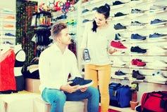Vendeur féminin démontrant des espadrilles au client dans le magasin de sports Image stock