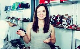 Vendeur féminin dans la boutique de chaussures Photo stock