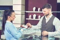 Vendeur féminin dans le magasin de bijoux montrant l'anneau d'or pour l'acheteur Photo stock