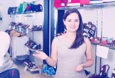 Vendeur féminin dans le magasin de chaussures Photos stock