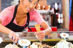 Vendeur féminin dans le salon avec le cornet de crème glacée Photo stock