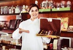 Vendeur féminin offrant la grande boîte de chocolats Photos stock
