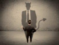 Vendeur faisant face à sa propre ombre de diable Photographie stock
