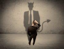 Vendeur faisant face à sa propre ombre de diable Photos stock
