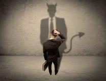 Vendeur faisant face à sa propre ombre de diable Photos libres de droits