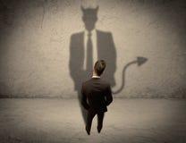 Vendeur faisant face à sa propre ombre de diable Images stock