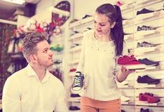 Vendeur heureux aidant l'homme en choisissant des espadrilles Photo stock