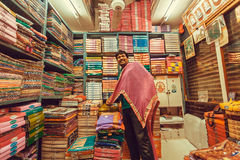 Vendeur heureux avec l'attente de textile des clients sur le marché traditionnel avec l'habillement femelle Photographie stock libre de droits