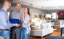 Vendeur heureux montrant à clients le catalogue produit images stock