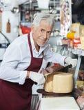 Vendeur heureux Slicing Whole Cheese avec le couteau dans la boutique Image libre de droits