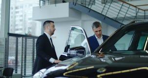 Vendeur invitant l'acheteur potentiel à obtenir dans la voiture photo libre de droits