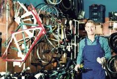 Vendeur masculin dans de nouvelles mains de roue de bicyclette de cueillette uniforme image stock