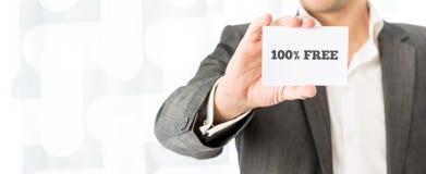 Vendeur montrant une carte de visite professionnelle de visite blanche avec le signe gratuit de 100% Images stock