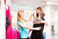 Vendeur parlant aux clients dans le magasin de mode Photo stock