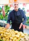 Vendeur posant près de l'affichage avec la pomme de terre Image stock