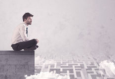 Vendeur s'asseyant sur le dessus de toit résolvant le labyrinthe Photos libres de droits