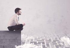 Vendeur s'asseyant sur le dessus de toit résolvant le labyrinthe Photographie stock libre de droits