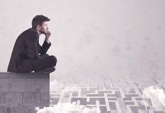 Vendeur s'asseyant sur le dessus de toit résolvant le labyrinthe Image stock