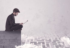 Vendeur s'asseyant sur le dessus de toit résolvant le labyrinthe Images libres de droits
