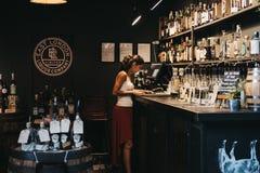 Vendeur s'chargeant des écritures à un stand est de Londres Liquor Company au marché de ville, Londres, R-U image stock